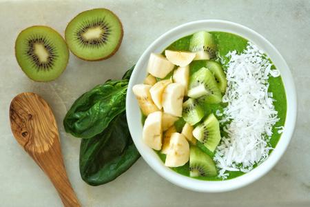 Groene smoothie kom met spinazie bananen kiwi en kokos met lepel op een witte marmeren achtergrond Stockfoto