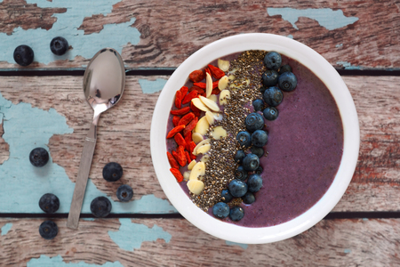 Nutritious blueberry smoothie bowl with goji berries almonds and chia seeds on a rustic old wood background