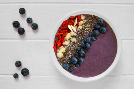 chia seed: Nutritious blueberry smoothie bowl with goji berries almonds and chia seeds on white wood with fresh berries