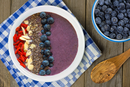 Blueberry smoothie bowl with almonds goji berries and chia seeds on a wood table with fresh blueberries