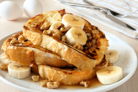 Plate of delicious French toast with bananas walnuts and dripping maple syrup
