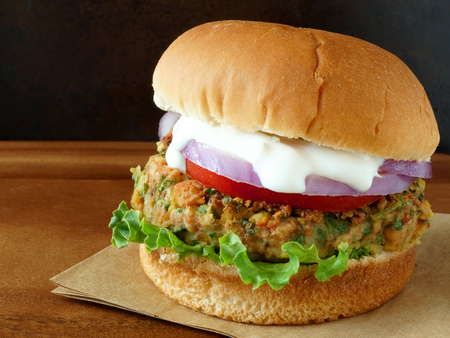 burger: Warm falafel burger with lettuce tomato red onion and tzatziki sauce on wood with dark background Stock Photo