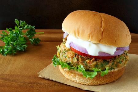 hamburguesa: Hamburguesa de falafel caliente con lechuga tomate cebolla roja y salsa tzatziki en la madera con fondo oscuro