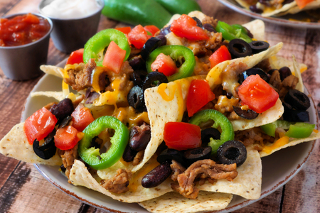nachos: Plate of Mexican nachos loaded with ground meat jalapenos tomatoes beans and melted cheese
