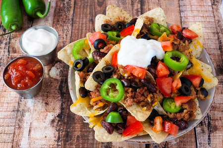 melted cheese: Plate of Mexican nacho chips topped with sour cream ground meat jalapenos tomatoes beans and melted cheese Stock Photo