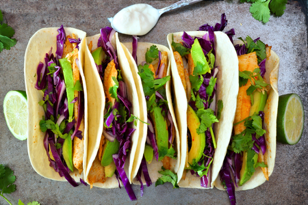 Spicy fish tacos with red cabbage lime slaw and avocado overhead view on rustic tray