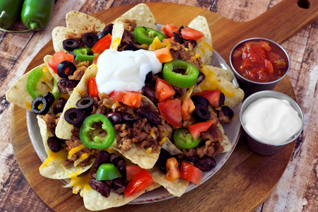 chips and salsa: Mexican nacho chips topped with ground meat jalapenos tomatoes beans and melted cheese with sour cream and salsa on a wooden paddle board Stock Photo