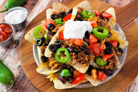 plates of food: Mexican nacho chips topped with sour cream ground meat jalapenos tomatoes beans and melted cheese on a wooden paddle board