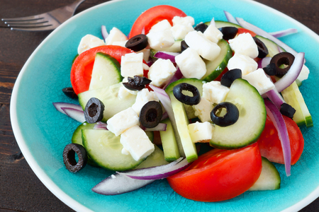 Fresh Greek Salad close up on a blue plate with dark wood background photo