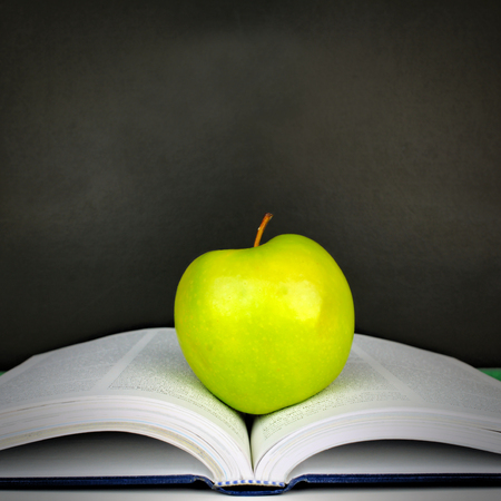 Green apple resting on open textbook against a blackboard background