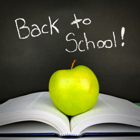 green and black: Green apple resting on open textbook against a blackboard with Back to School text Stock Photo
