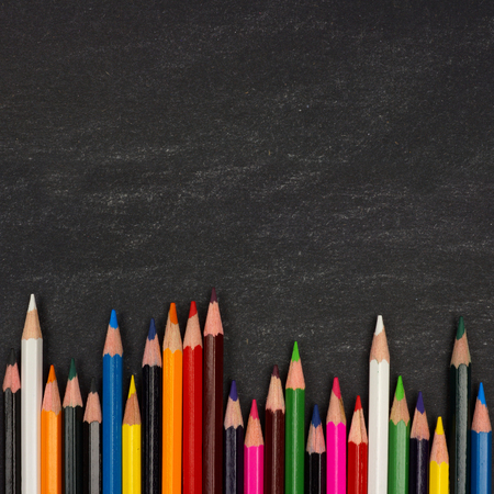 elementary education: Bottom border of colorful pencil crayons against a blackboard background