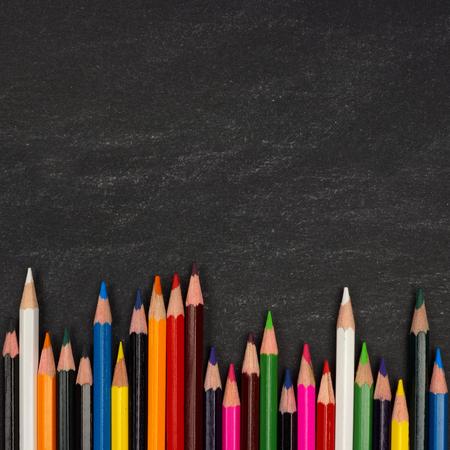 Onderste rand van kleurrijke potloodkleurpotloden tegen een schoolbord achtergrond Stockfoto