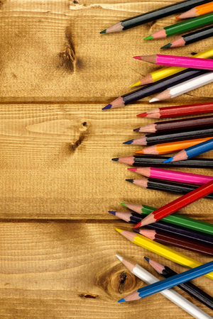scattered: Side border of colorful pencil crayons against a wood background