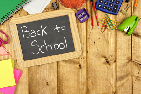 Back to School on a chalkboard with wood background and school supplies corner border