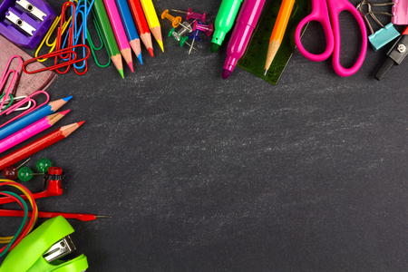 School supplies top corner border on a chalkboard background