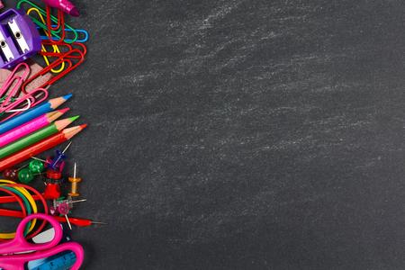 eğitim: Bir kara tahta arka plan üzerinde okul malzemeleri yan sınır