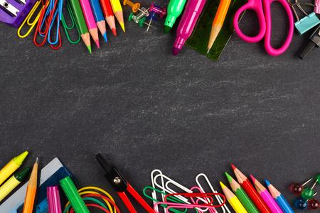 utiles escolares: Los útiles escolares doble fronterizos sobre un fondo de pizarra Foto de archivo