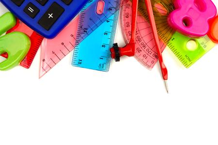 papírnictví: Hranice barevných školních pomůcek s tématikou matematiky na bílém pozadí