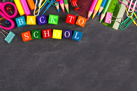 Colorful Back to School wooden blocks with school supplies top border on a chalkboard Stock Photo