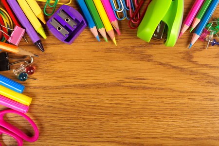 School supplies top corner border on a wood desk background
