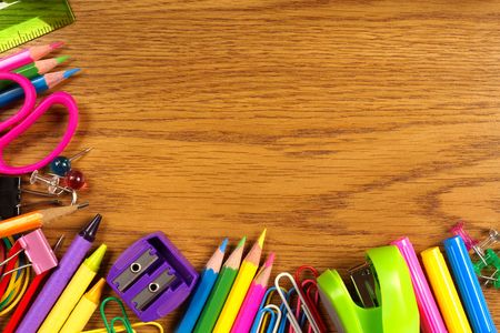 learning materials: School supplies bottom corner border on a wood desk background