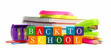 白い背景の上の学用品のグループと学校の木のおもちゃブロックにカラフルなバック