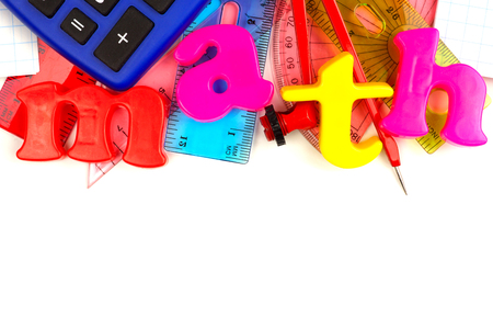 Toy magnetic letters spelling math with a math-themed school supplies top border over white Stock Photo