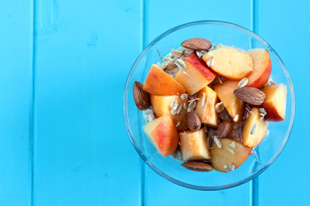 overnight: Healthy overnight oats with fresh peaches and almonds, overhead view on a blue wood background Stock Photo