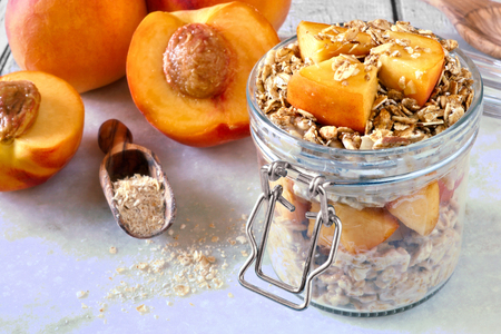 overnight: Breakfast oats with fresh peaches and granola in snap lid glass jar on white marble