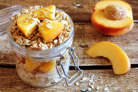 clamped: Overnight oats with fresh peaches and granola in snap lid glass jar on rustic wood
