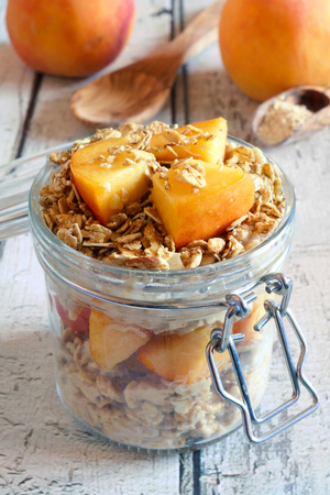 overnight: Overnight breakfast oats with peaches and granola in snap lid jar on white wood