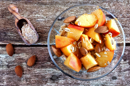 almond: Nutritious overnight oats with fresh peaches and almonds overhead view on a rustic wood background