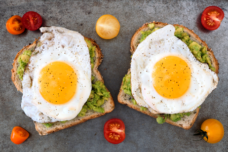 breakfast eggs: Open avocado, egg sandwiches on whole grain bread with tri-colored tomatoes on rustic baking tray Stock Photo