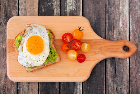 sliced: Avocado, egg open sandwich on whole grain bread with cherry tomatoes on paddle board with rustic wood background