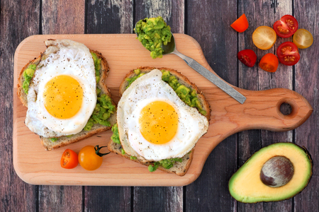 Avocado egg open sandwiches on whole grain bread with tomatoes on paddle board with rustic wood table Imagens