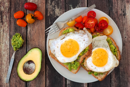Healthy avocado, egg open sandwiches on a plate with cherry tomatoes on a rustic wood background 写真素材