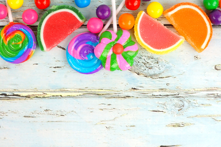 gumballs: Top border of varied colorful candies against a rustic wooden background
