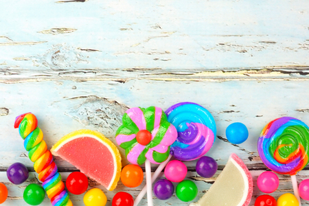 candy border: Bottom border of varied colorful candies against a rustic wooden background Stock Photo