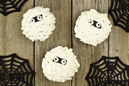 Group of Halloween mummy cupcakes against a wood background