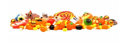 カラフルなハロウィーンのキャンディやお菓子、白い背景の上の長い杭