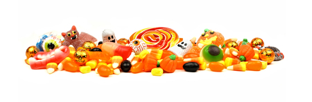 halloween eyeball: Long pile of colorful Halloween candy and sweets over a white background
