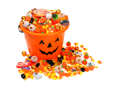 halloween eyeball: Halloween Jack o Lantern candy pail overflowing with assorted sweets over a white background Stock Photo