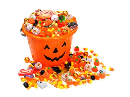 Halloween-Kürbislaterne Candy Eimer überfüllt mit verschiedenen Süßigkeiten auf einem weißen Hintergrund Standard-Bild