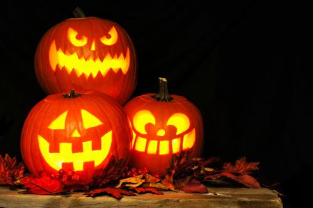 Gestapelde Halloween Jack o Lantaarns 's nachts verlicht met oude hout en de herfstbladeren Stockfoto