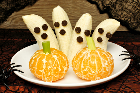 treat: Healthy Halloween treats, banana ghosts and orange pumpkins, on a plate with holiday decor