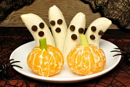 Ossequi sani di Halloween, fantasmi banana e zucche arancioni, su un piatto con decorazione di festa Archivio Fotografico