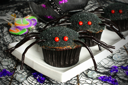 Halloween spider cupcakes on a plate with candy and holiday decor