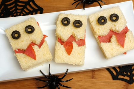 Fun Halloween monster sandwiches on a plate with wood background