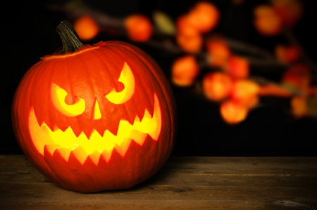 Spooky Halloween Jack o Lantern at night on wood with autumn leaves in background Stock Photo